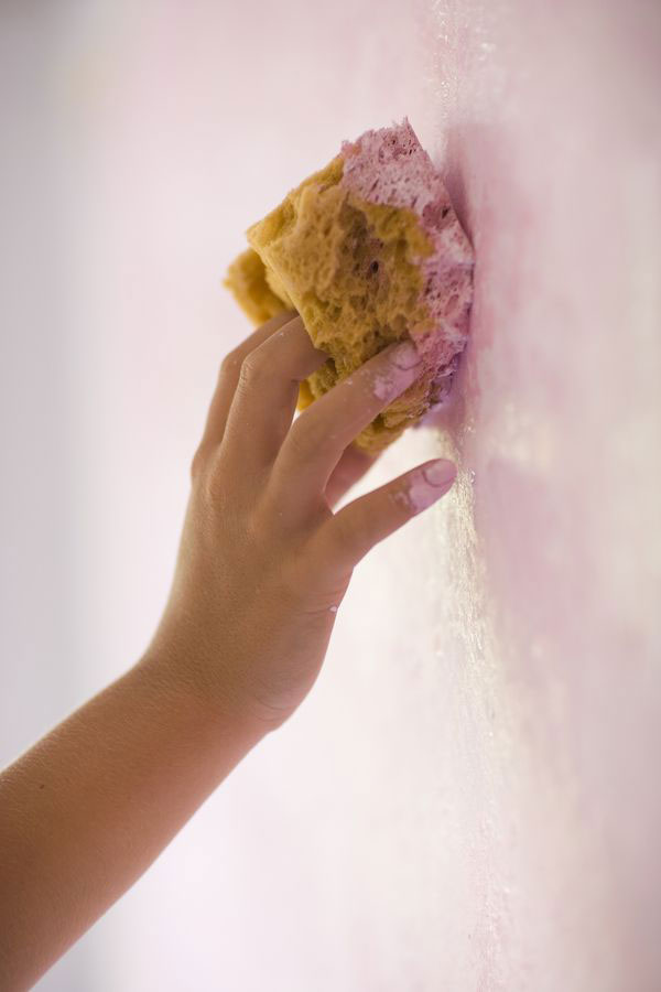 a hand texture-a-wall-with-a-sponge